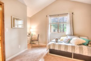 Interior shot of a residential bedroom with wood-trimmed windows