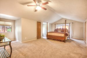 Interior shot of a master bedroom with white walls and carpeting, and a large king bed