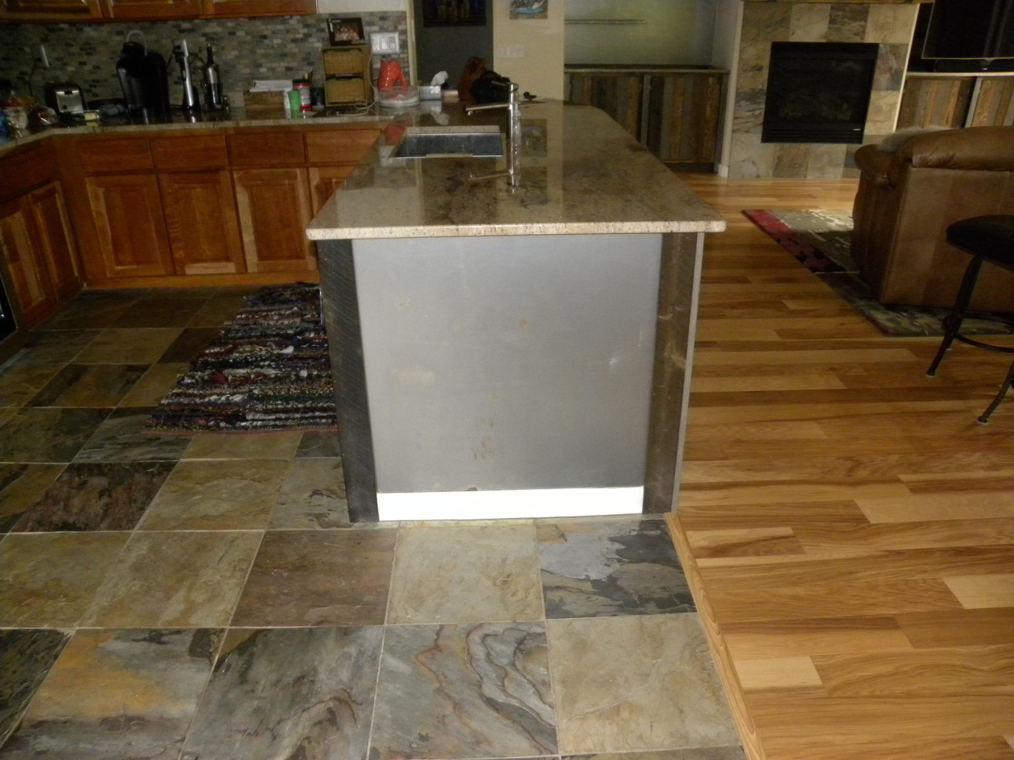 Newly remodeled kitchen with tile flooting, granite countertops, and wooden cabinets