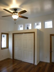 Interior shot of a wooden framed closet with matching windows and door framing.