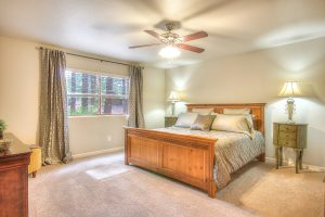 Interior photo of a master bedroom with a king bed, white walls, and white carpeting.