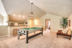 Interior photo of a carpeted leisure room with a pool table, a love seat, and a custom full sized bar.