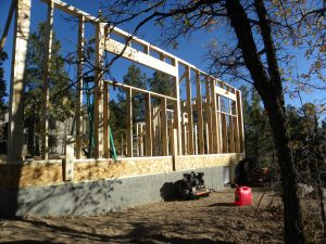 Photo of a house construction site in a wooded neighborhood