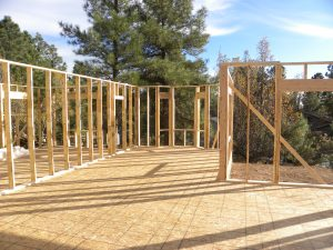 Photo of house construction in a forested neighborhood.
