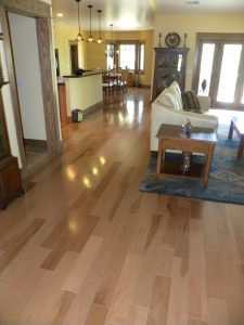 Interior photo of new wooden flooring in an open dining room and kitchen area.
