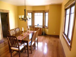 Photo of a dining room with large, wood-trimmed windows and a rectangluar table for six.