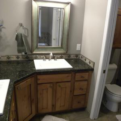A newly remodeled custom bathroom with black granite countertop, wooden cabinets, and white wood trimming
