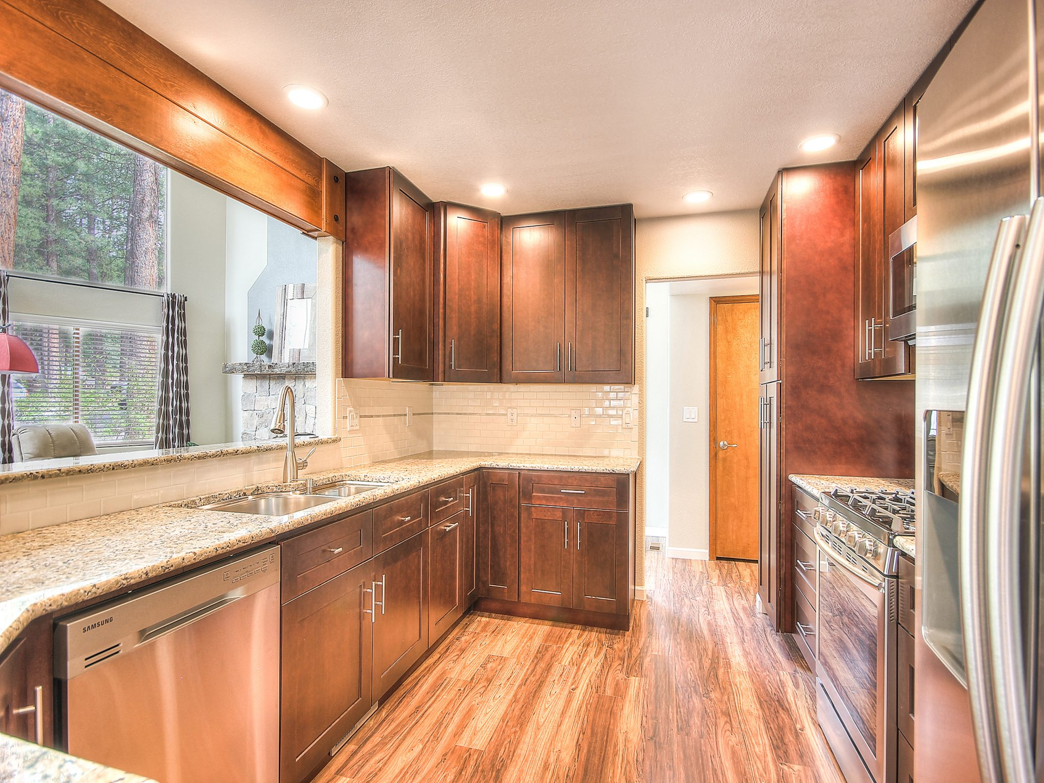 Interior shot of a newly remodeled kitchen with large wooden cabinets and white granite countertops
