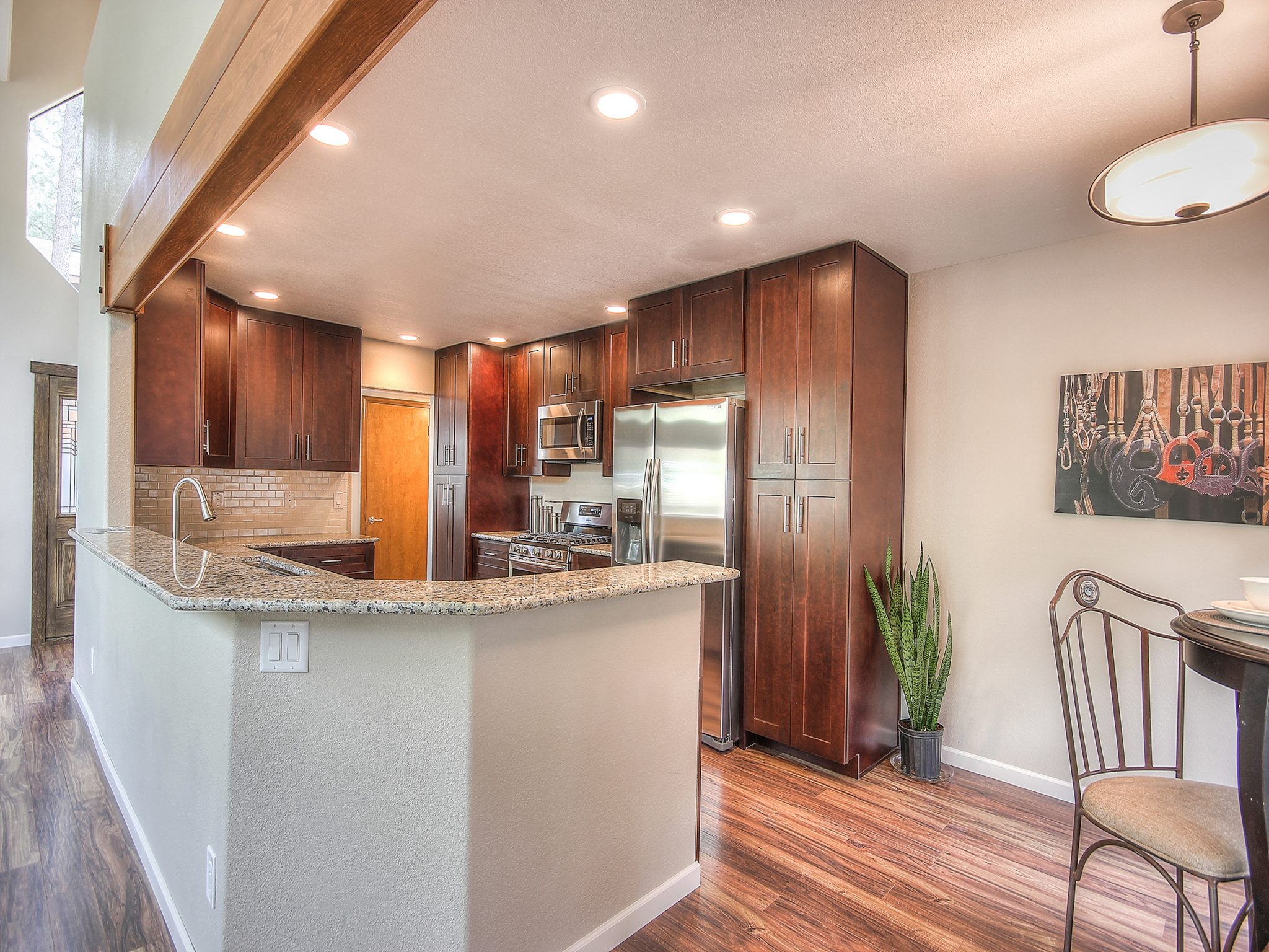 Interior shot of a newly remodeled kitchen with dark wooden cabinets and granite countertops
