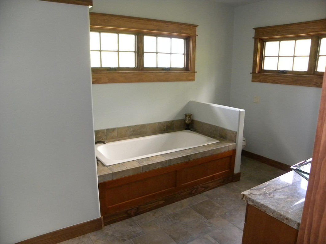 Custom designed bathroom with wood trimmed windows and granite counterspace