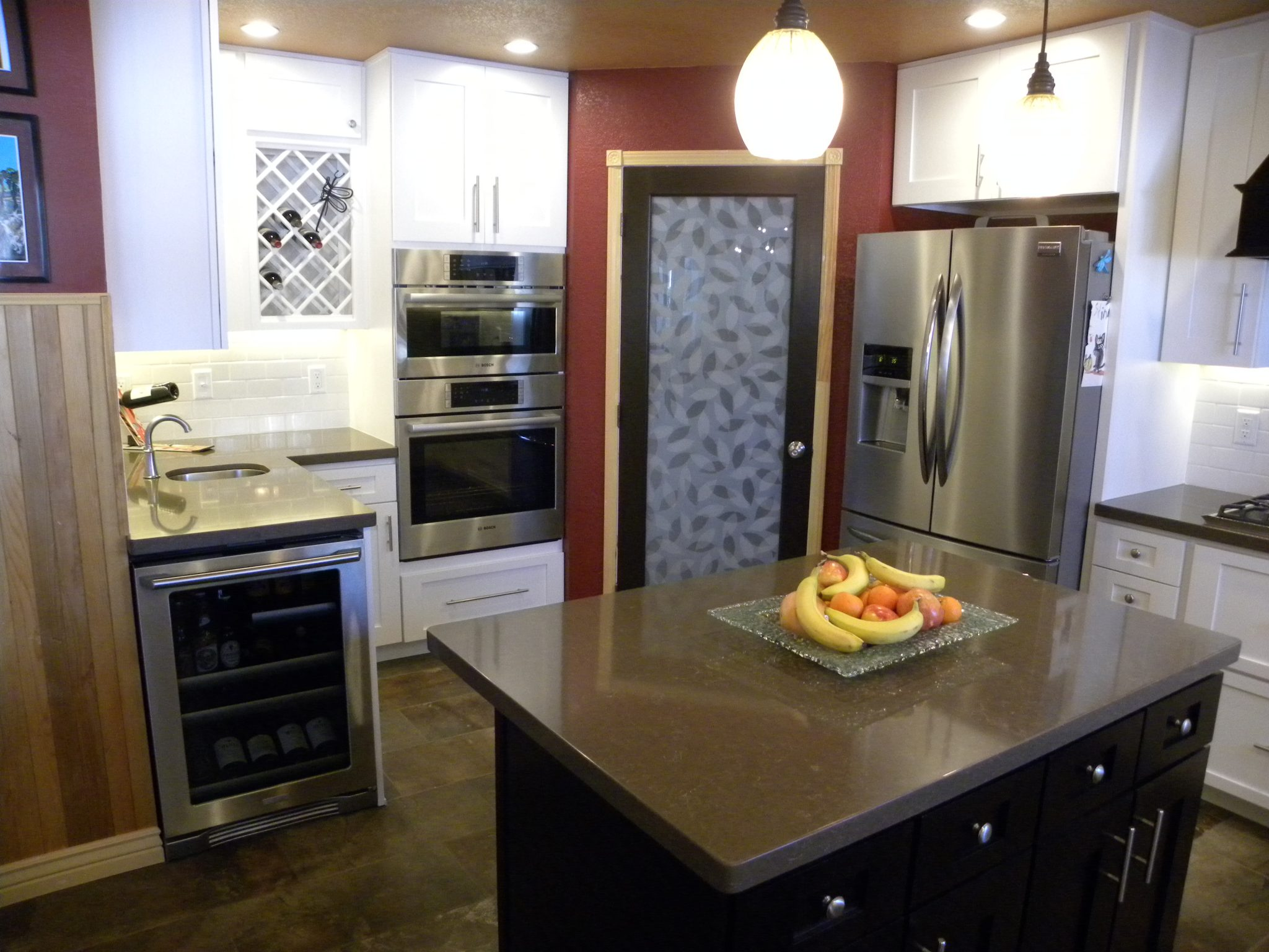 Interior shot of a newly remodeled kitchen with granite countertops, white wooden cabinets, and wood trimmed doors