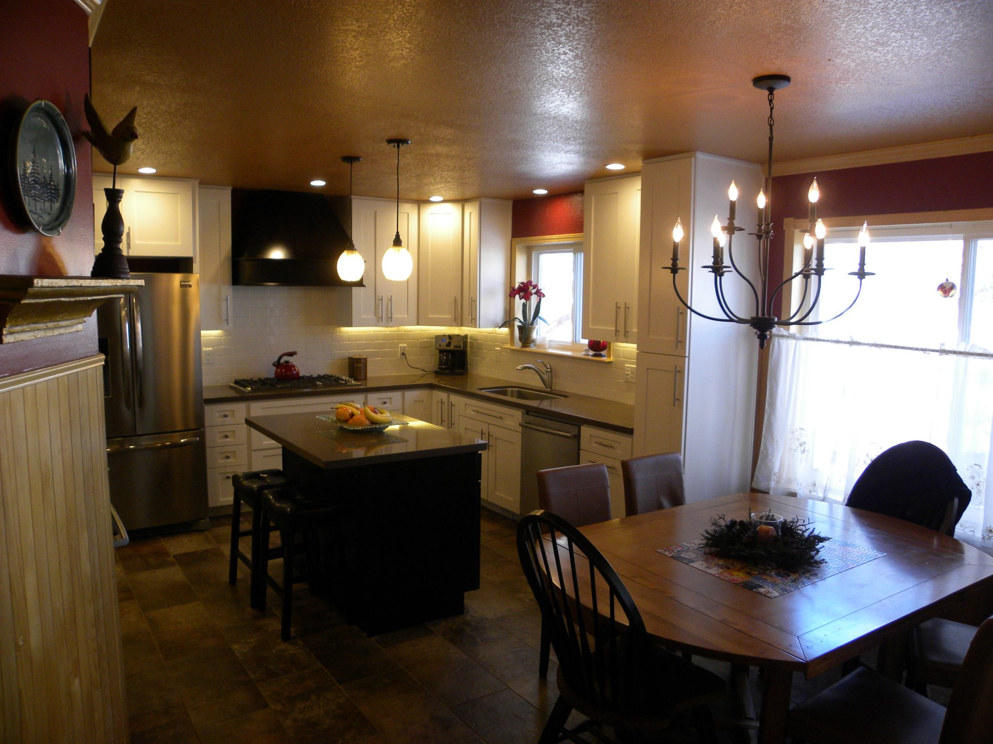 Interior shot of a newly remodeled kitchen with new lighting, granite countertops, and white wooden cabinets