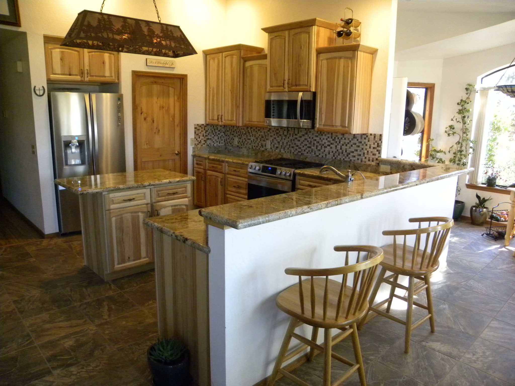 Interior shot of a newly remodeled kitchen with granite countertops and wooden cabinets
