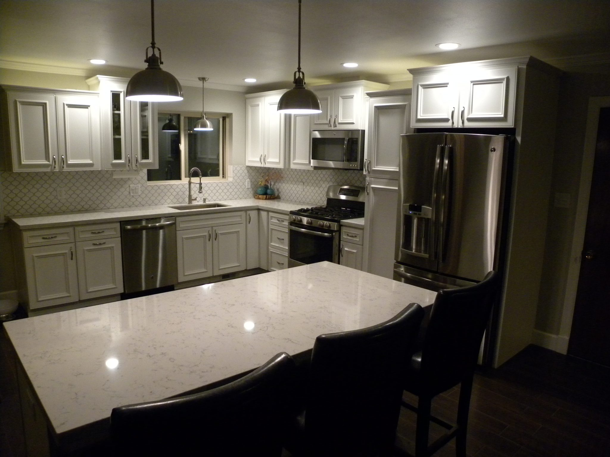 Interior shot of a newly remodeled kitchen with white granite countertops, white wooden cabinets, and matching white trim