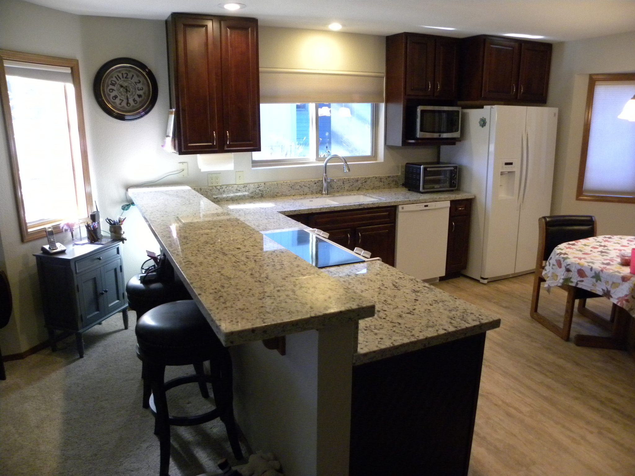Newly remodeled kitchen with dark wooden cabinets and speckled white granite countertops