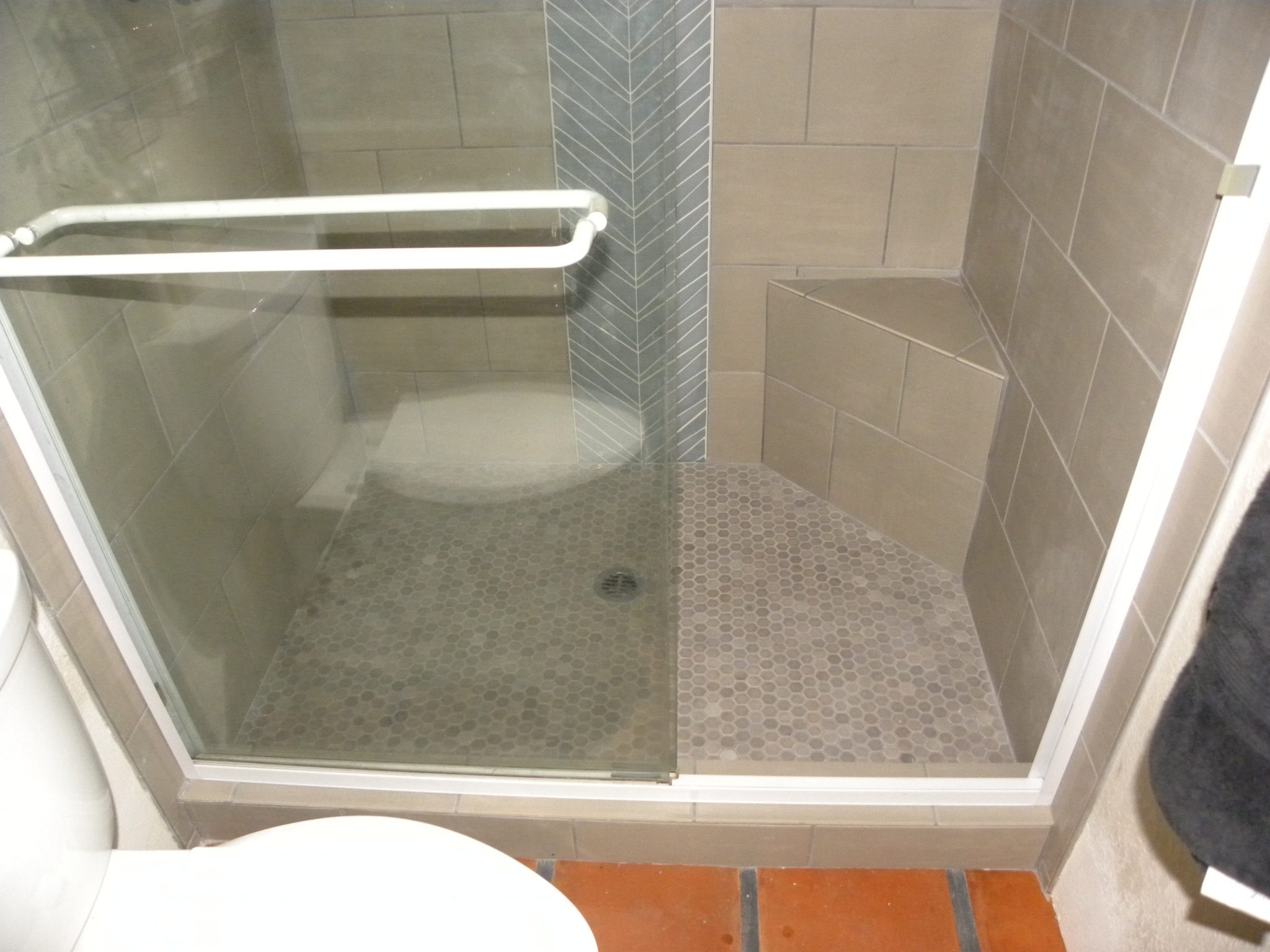 Interior shot of remodeled hower with white tiling and glass windows
