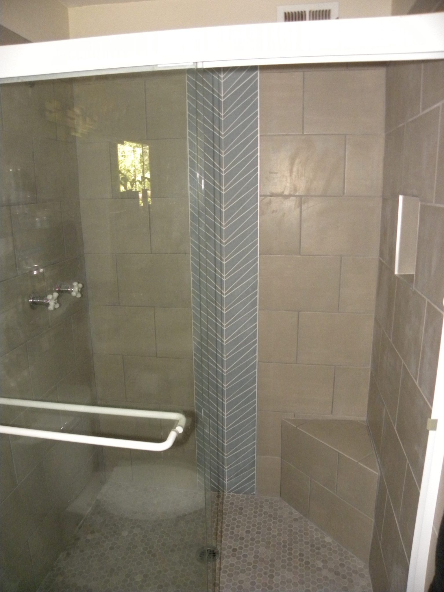 Interior shot of a custom designed shower with tan tiling and glass doors