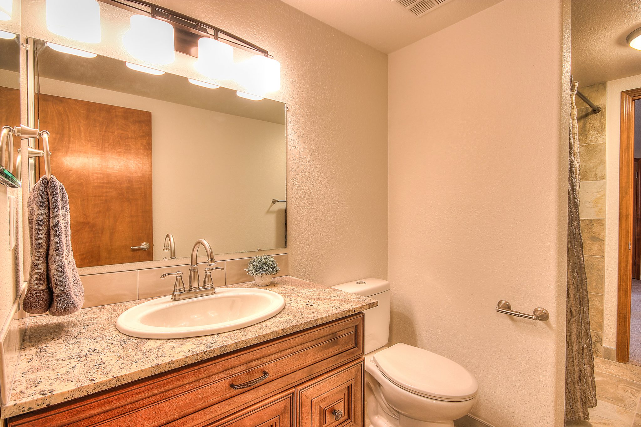 Interior shot of a newly remodeled bathroom with granite countertops and tan tiling