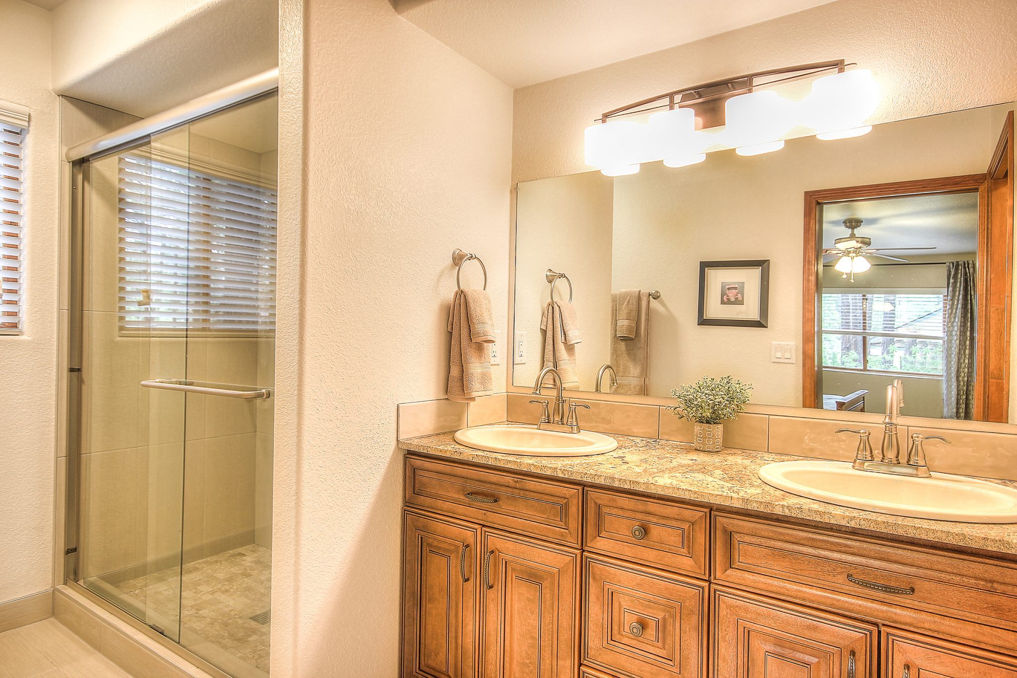 Interior shot of a newly remodeled bathroom with wooden cabinets, granite countertops, and a freshly tiled shower