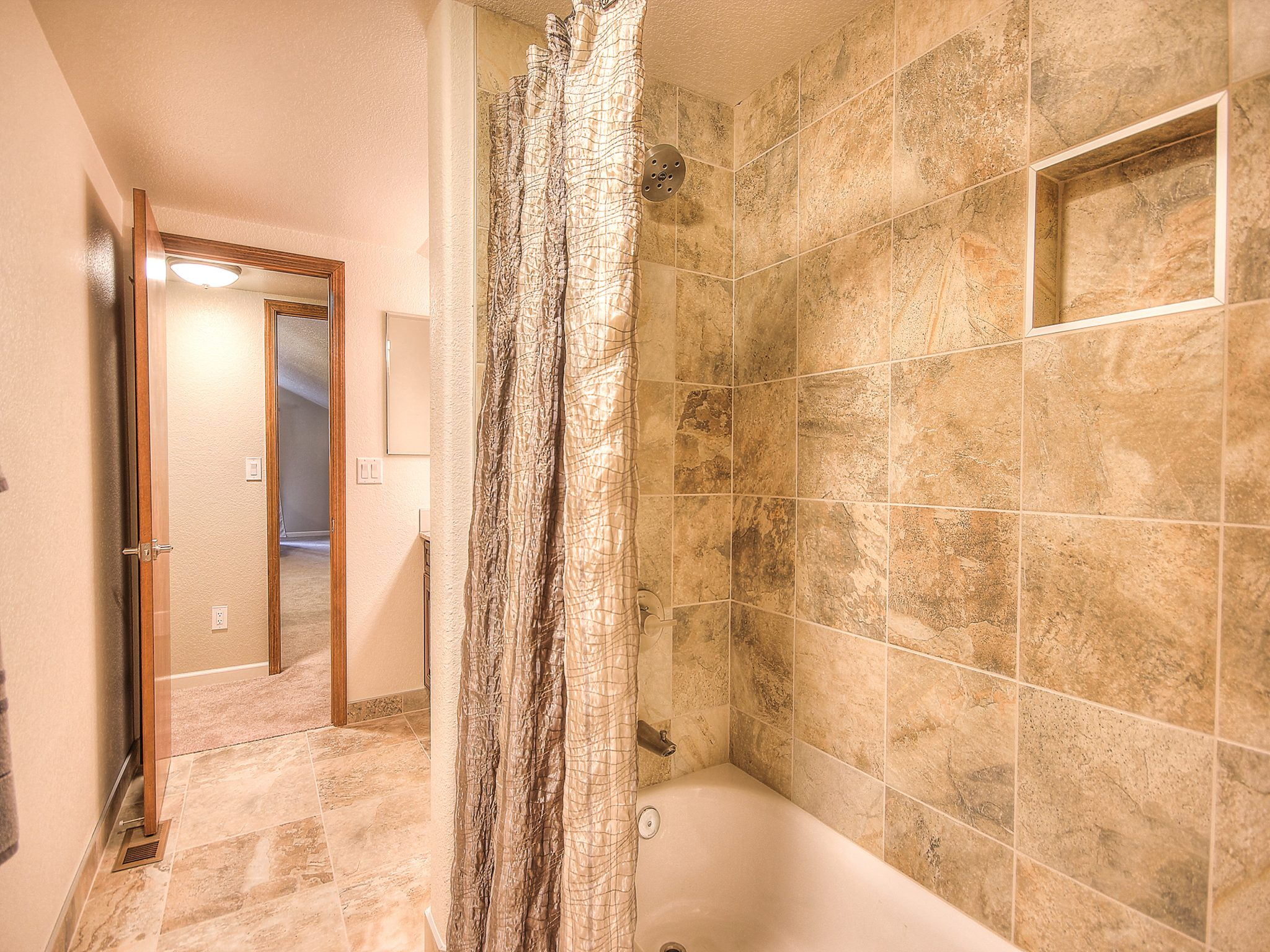 Interior shot of a custom designed bathroom with a tan-tiled shower and wood trimmed doorways