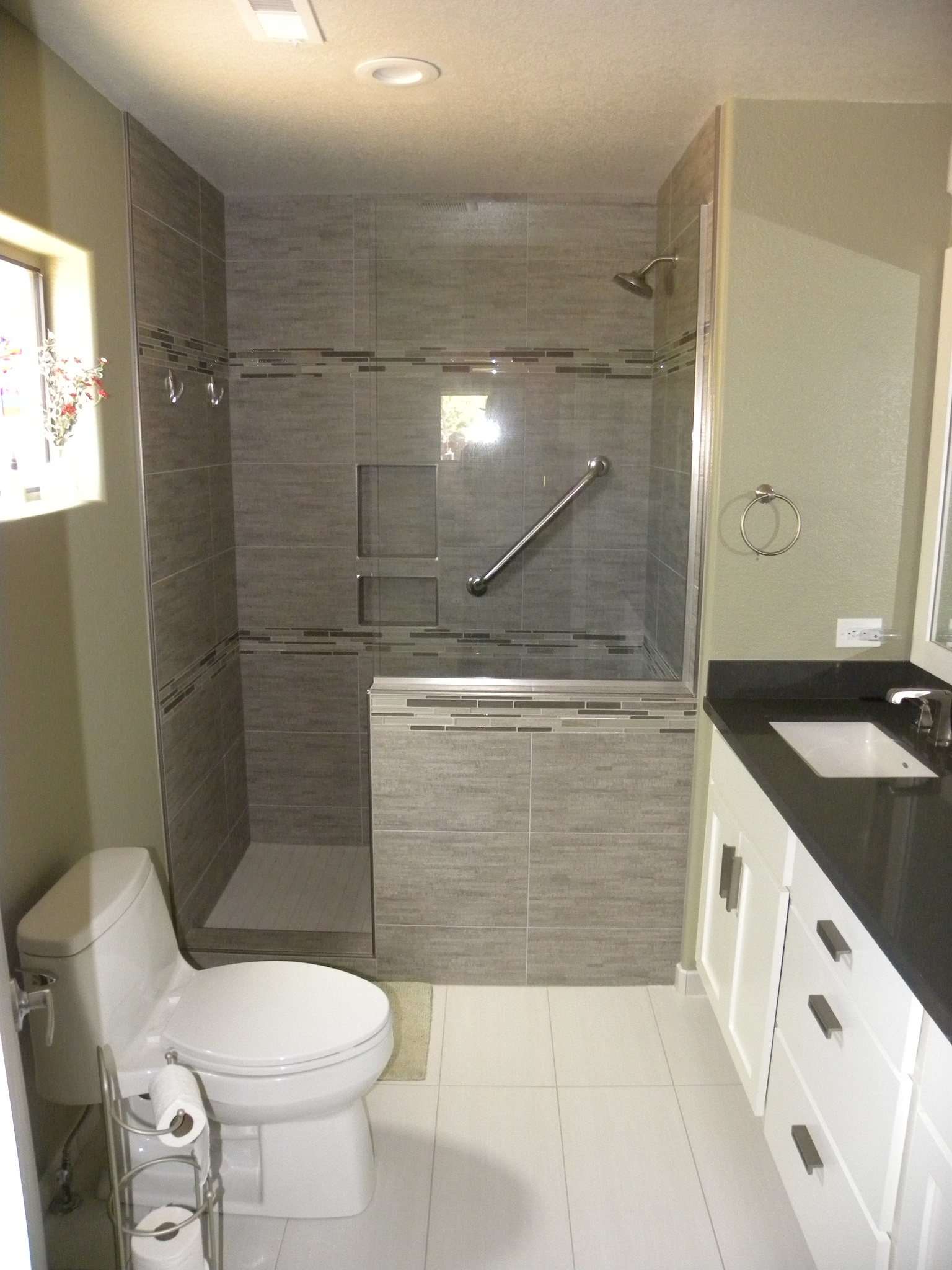 After photo of a custom residential bathroom with black countertops and white wooden cabinets, new white tiles, and a custom designed shower with gray tile, glass windows and doors, and specially design handles.
