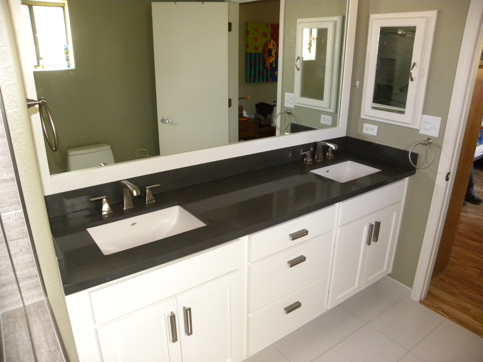 After photo of a custom designed bathroom with black countertops and white wooden cabinets in a residential bathroom.