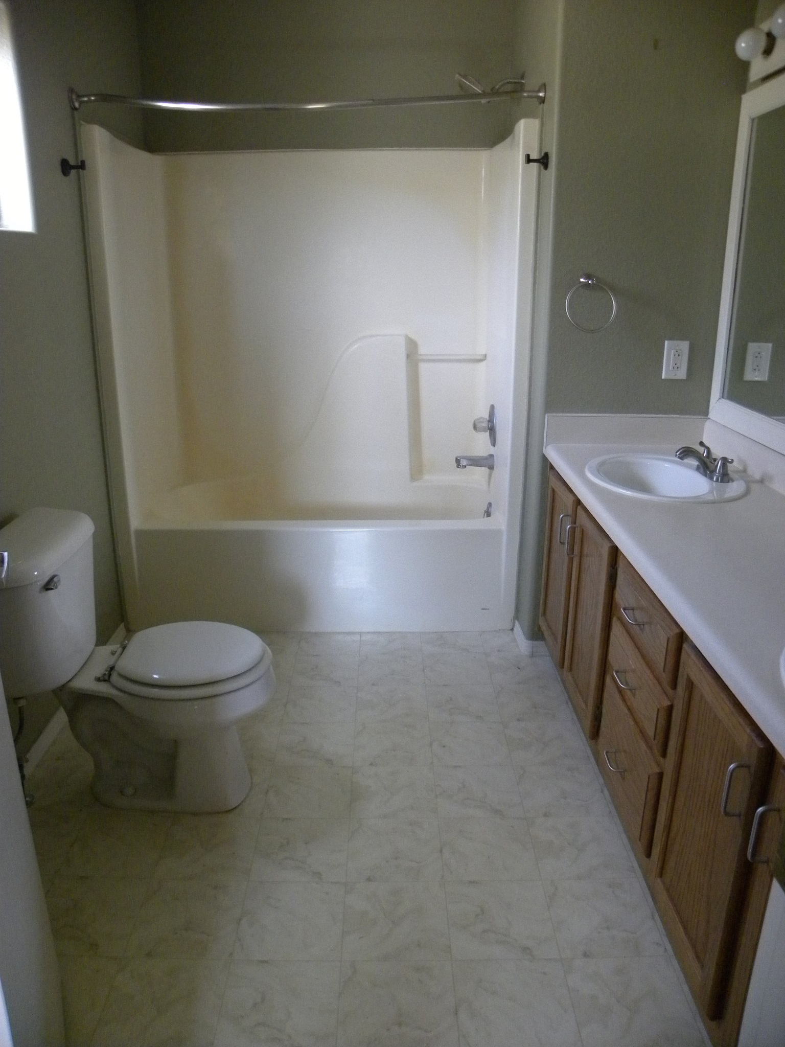 Before photo of a residential bathroom with white countertops and wooden cabinets, a white toilet, a white shower, and white marbled tiles.
