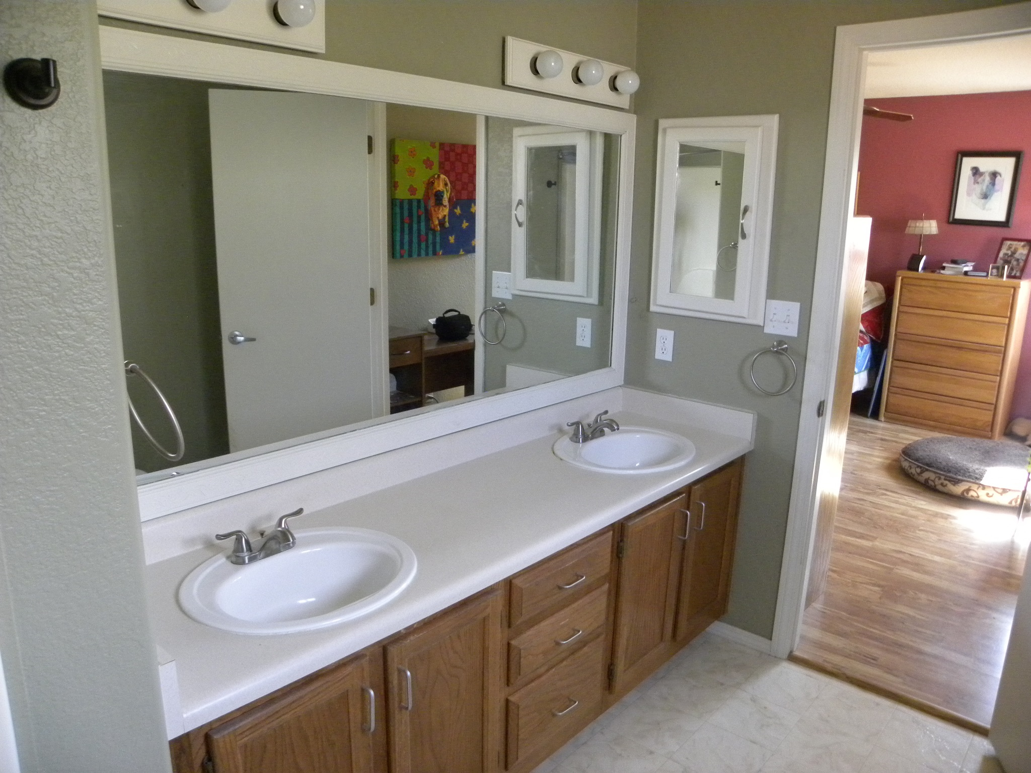 Before photo of a bathroom with white countertop and wooden cabinets in a residential bathroom.