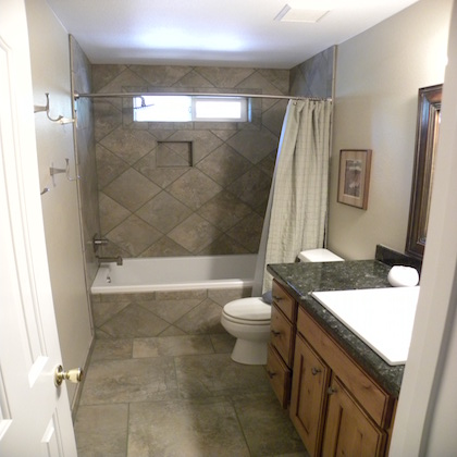 Interior shot of a custom designed bathroom with new tiling and floor cabinets