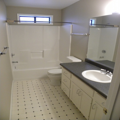 Interior before photo of a residential bathroom with tiling and cabinets