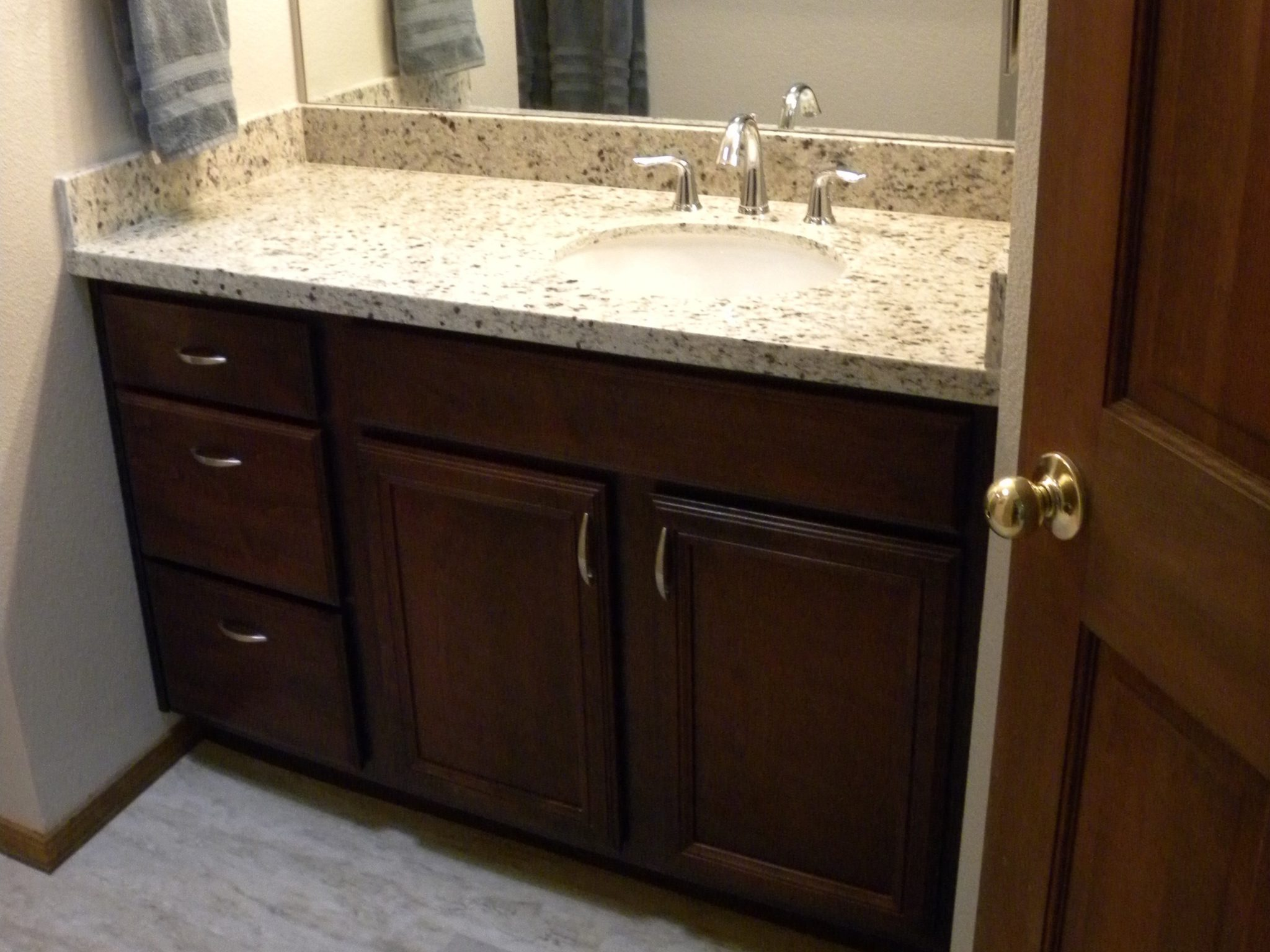 Remodeled bathroom sink with white countertops and dark wooden cabinets