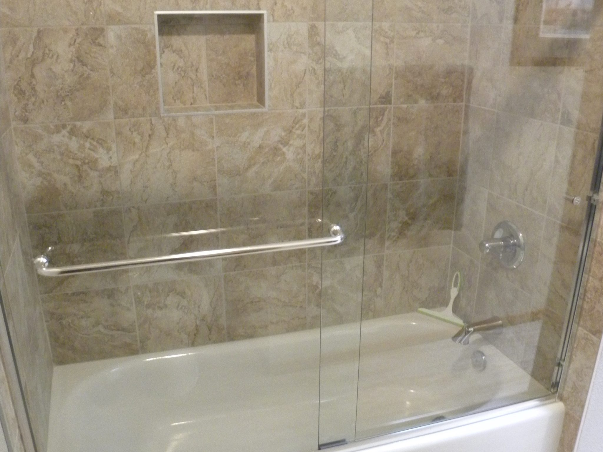 Interior shot of a newly remodeled custom shower with tan tiling and glass windows