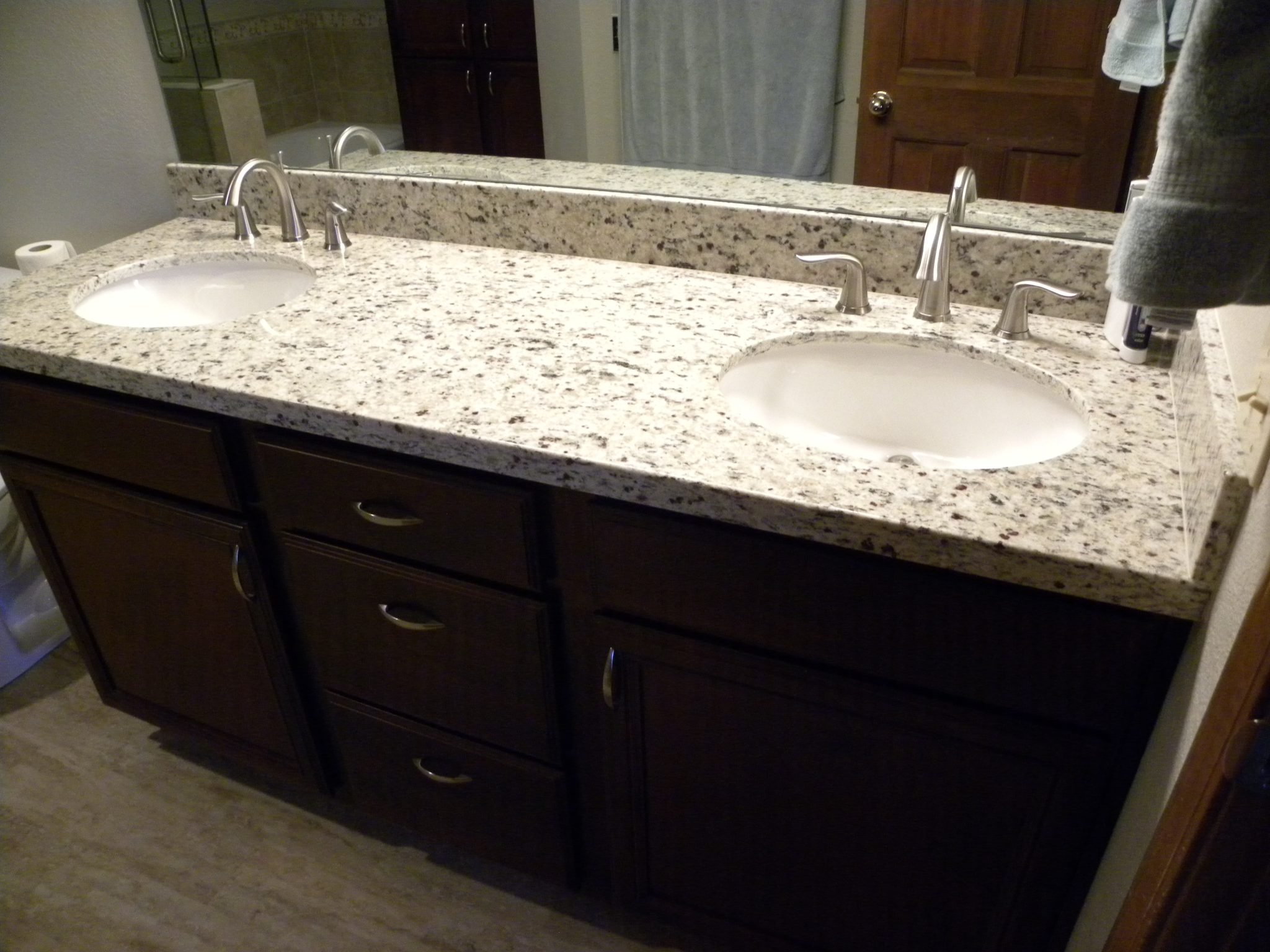 Interior shot of a newly remodeled bathroom with white granite countertops