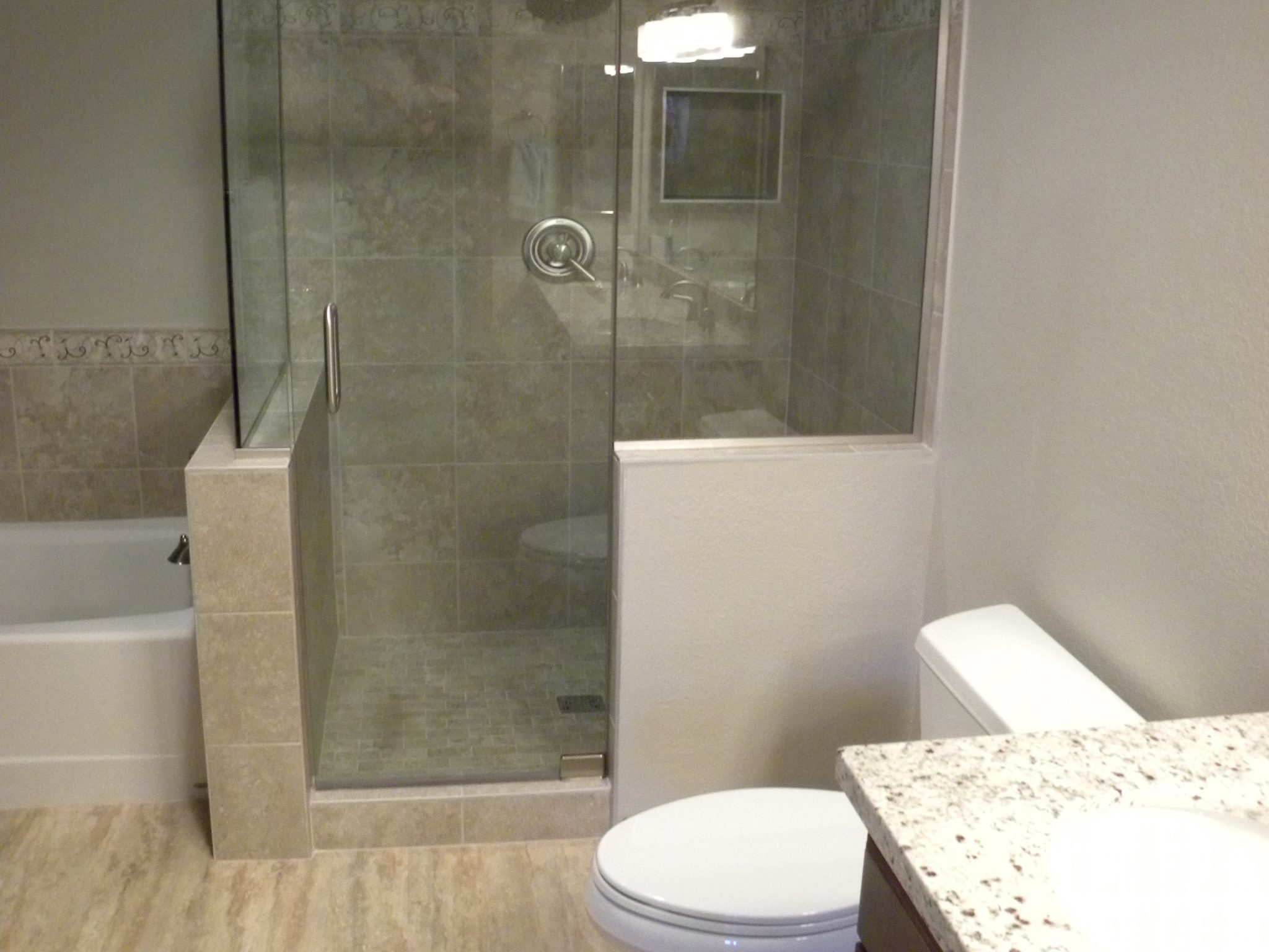 Interior shot of a newly remolded bathroom with a gray-tiled shower and white granite countertops