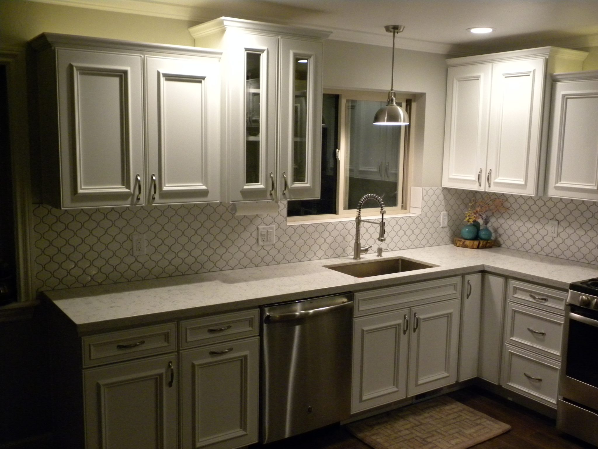 Remodeled kitchen with white granite countertops and white wooden cabinets and white trim