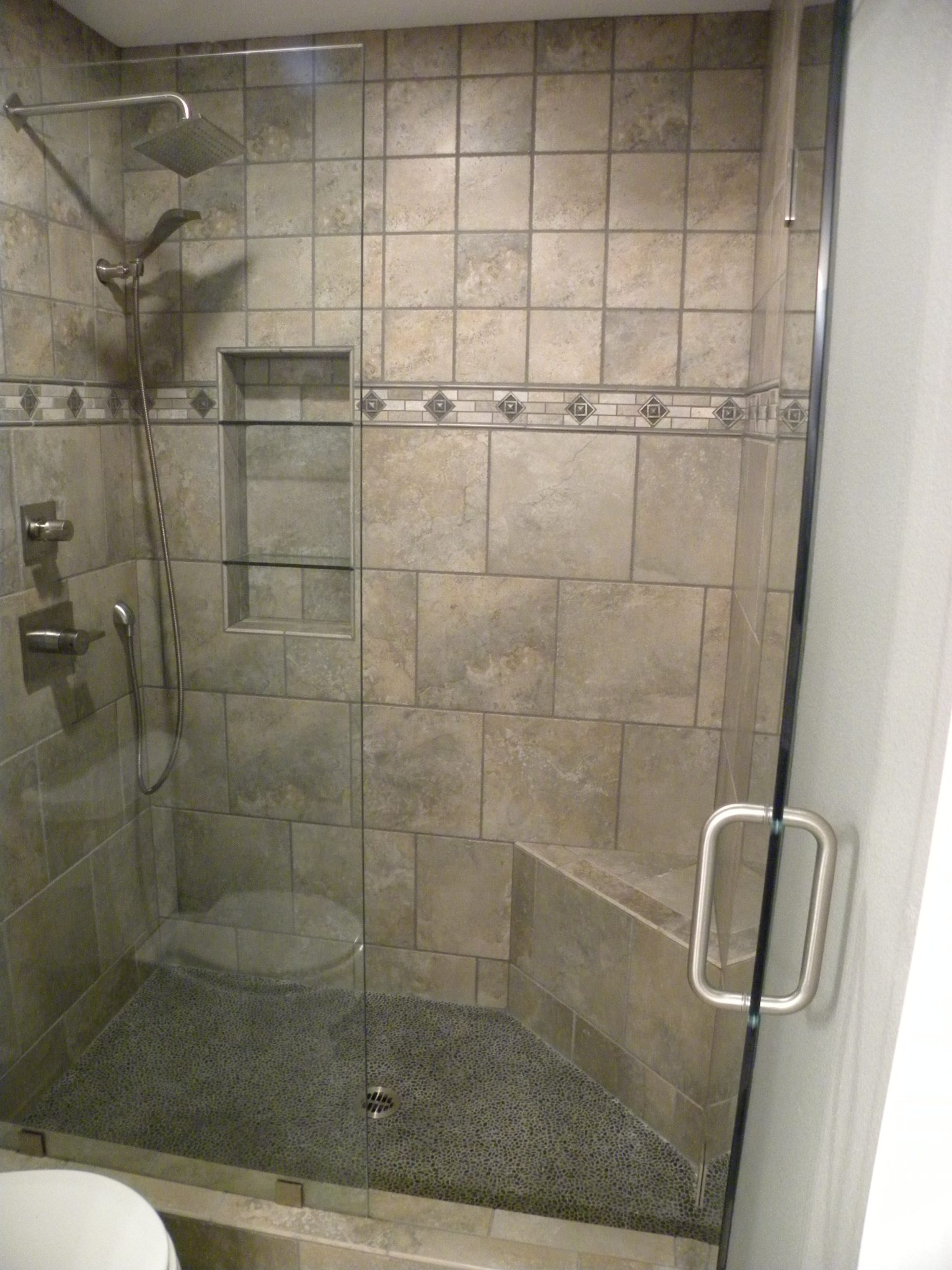 Interior shot of a custom designed shower with tan tiles and glass doors