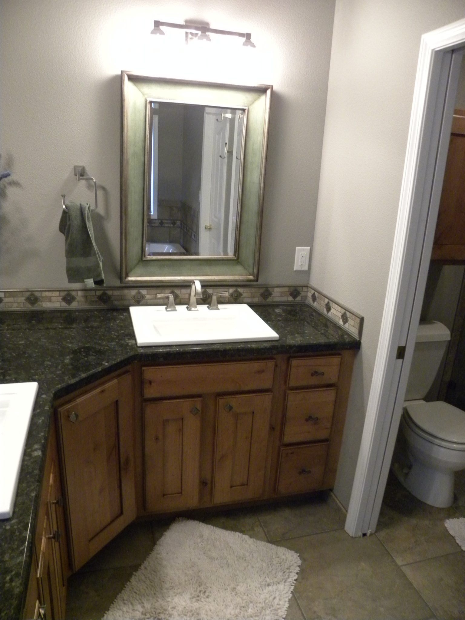 Interior shot of newly remolded bathroom with custom countertops and wood trimming