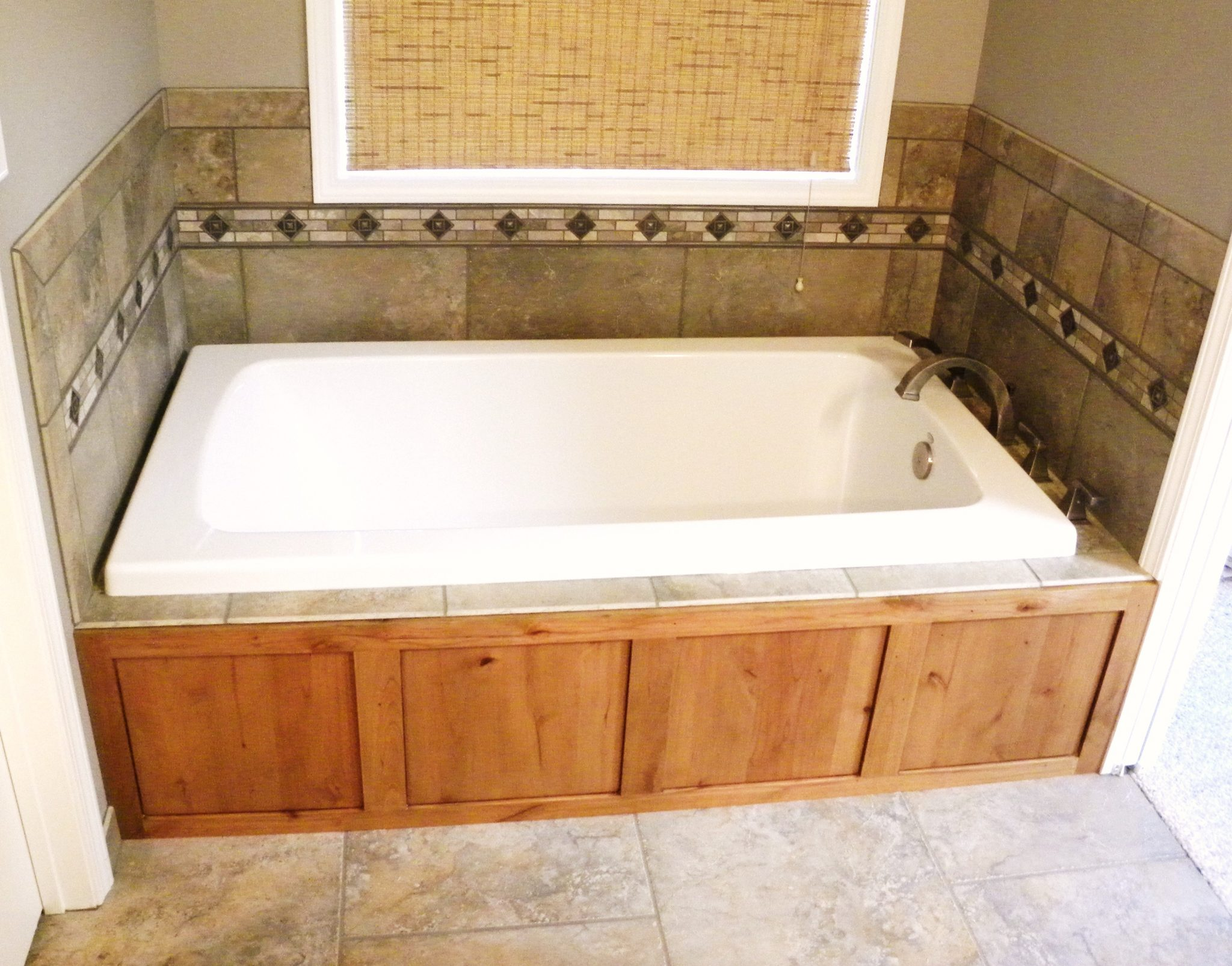 Interior shot of a newly remodeled custom bathtub with wood lining