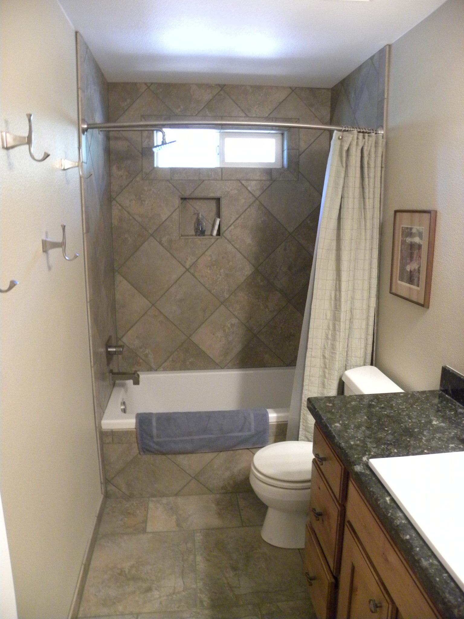 Interior shot of a custom designed bathroom with gray tiling and granite countertops
