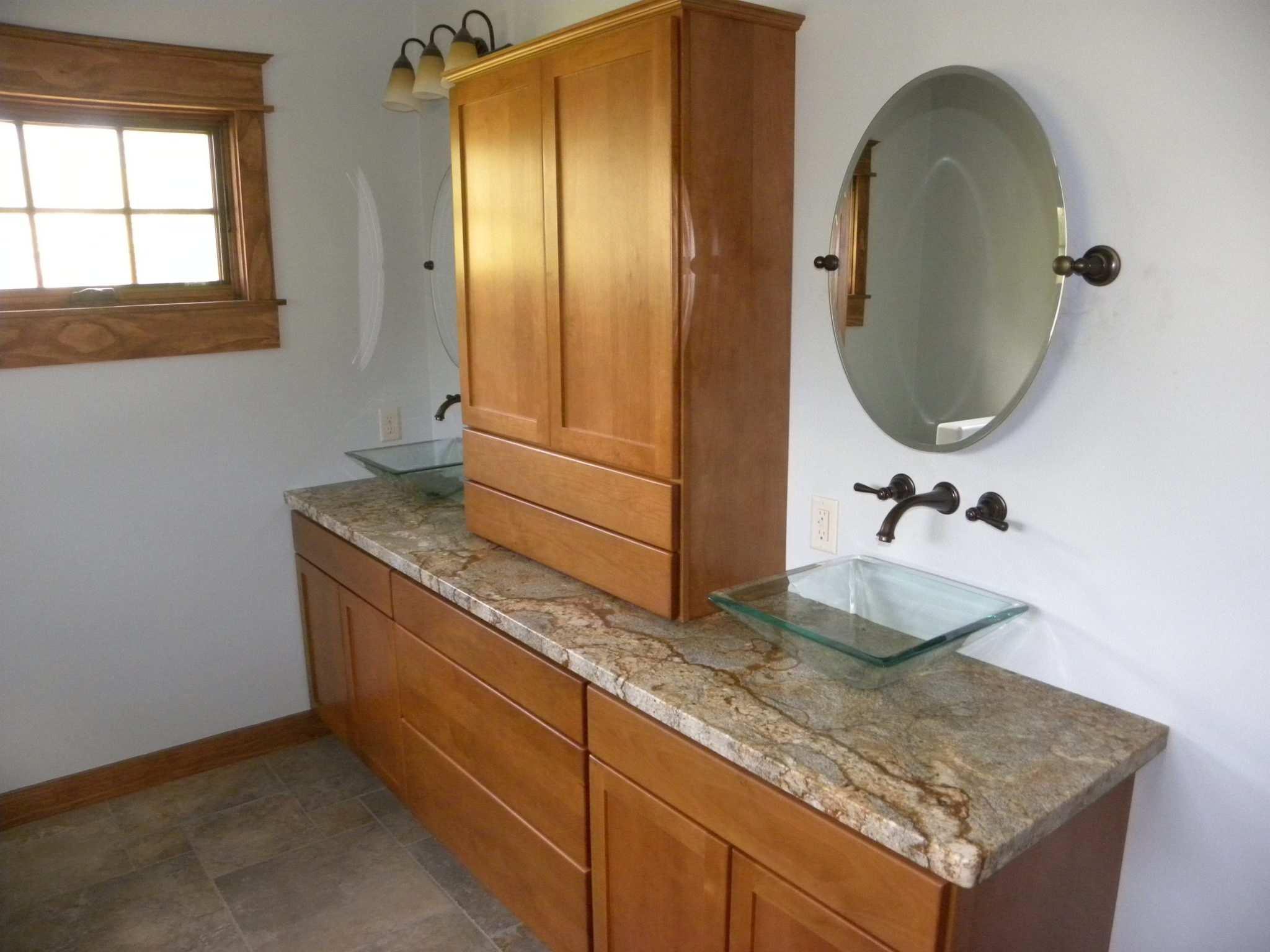 Interior shot of a newly remodeled bathroom with wooden cabinets and granite countertops