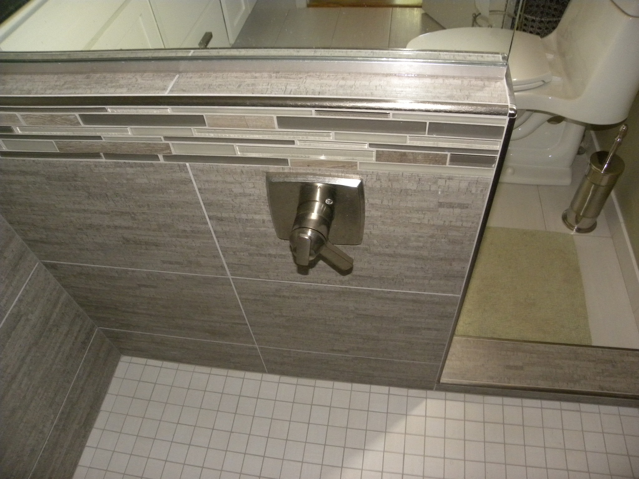 A custom built shower with gray tile and a specially designed shower handle