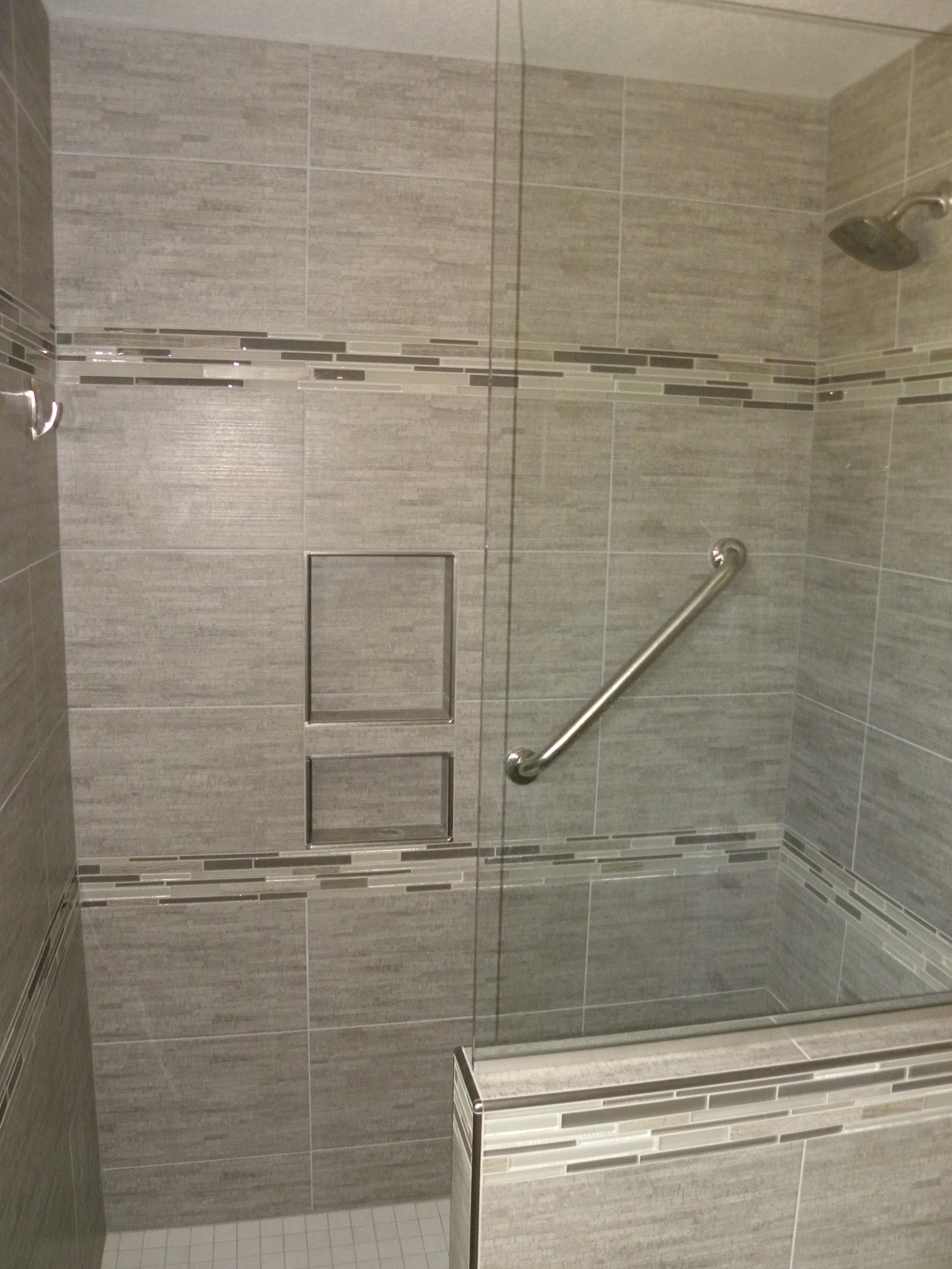 A custom built shower with a glass door and gray tile