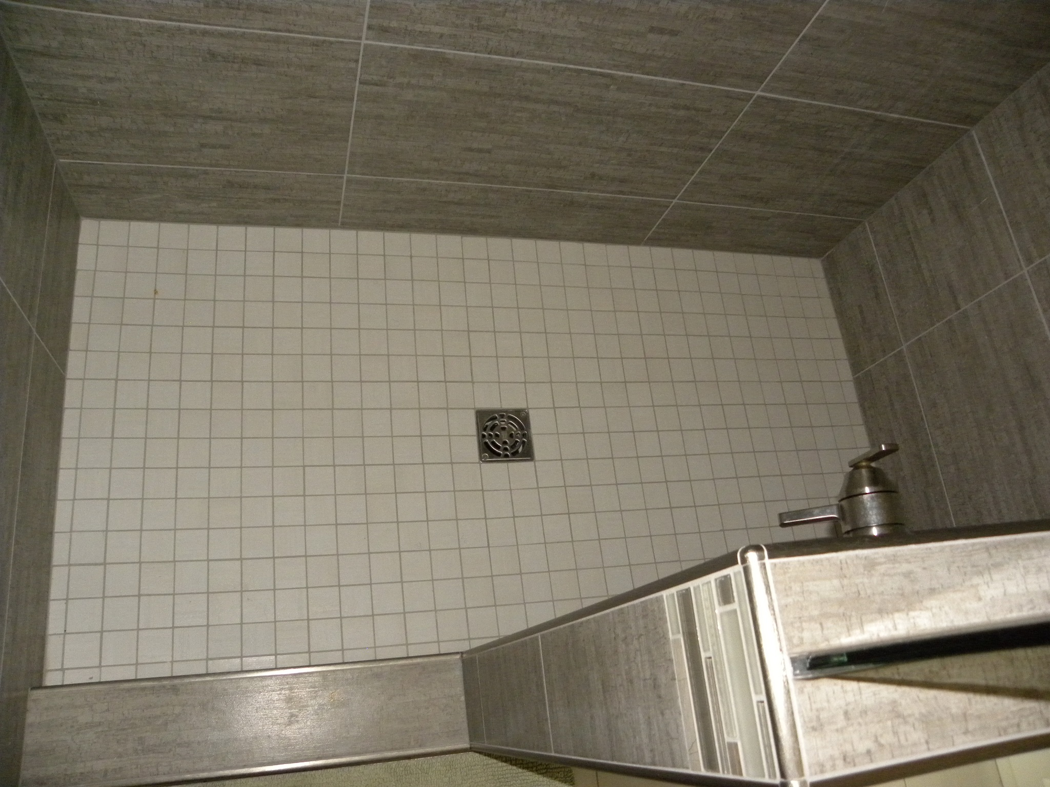 A custom built shower with gray and white tile and a specially designed shower handle